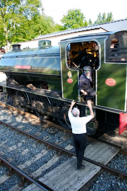 Signalman hands tablet to driver at Kent and East Sussex Railway