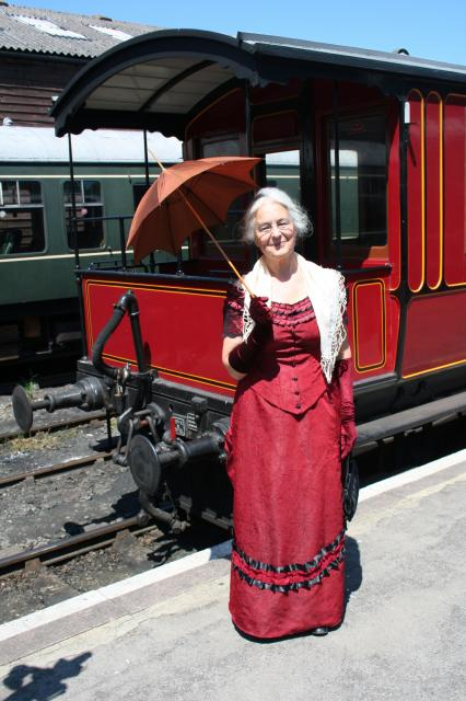 Victorian Lady dressed in red , standing by a Victorian coach, holding a parasol. (at the Kent and East Sussex Railway)