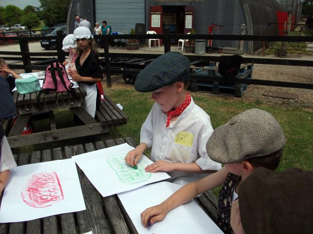 Two boys in Victorian costume enjoying taking engine plate rubbings  (at the Kent and East Sussex Railway during a Victorian experience day)
