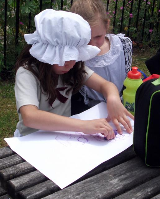 Children in Victorian costume taking engine plate rubbings  (at the Kent and East Sussex Railway during a Victorian experience day)