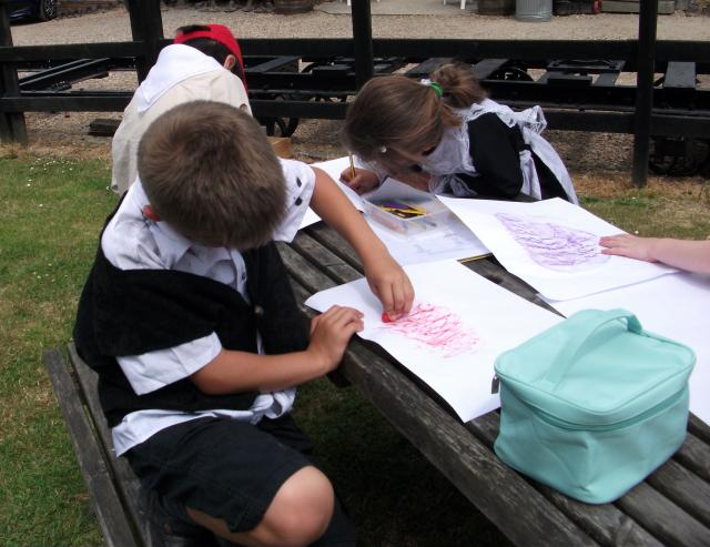 Children in Victorian costume taking wagon plate rubbings  (at the Kent and East Sussex Railway during a Victorian experience day)