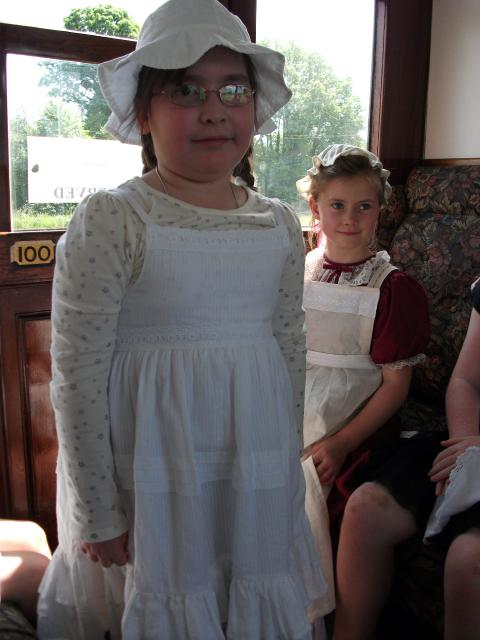 A girl in Victorian costume stands in a Victorian carriage.  (at the Kent and East Sussex Railway)