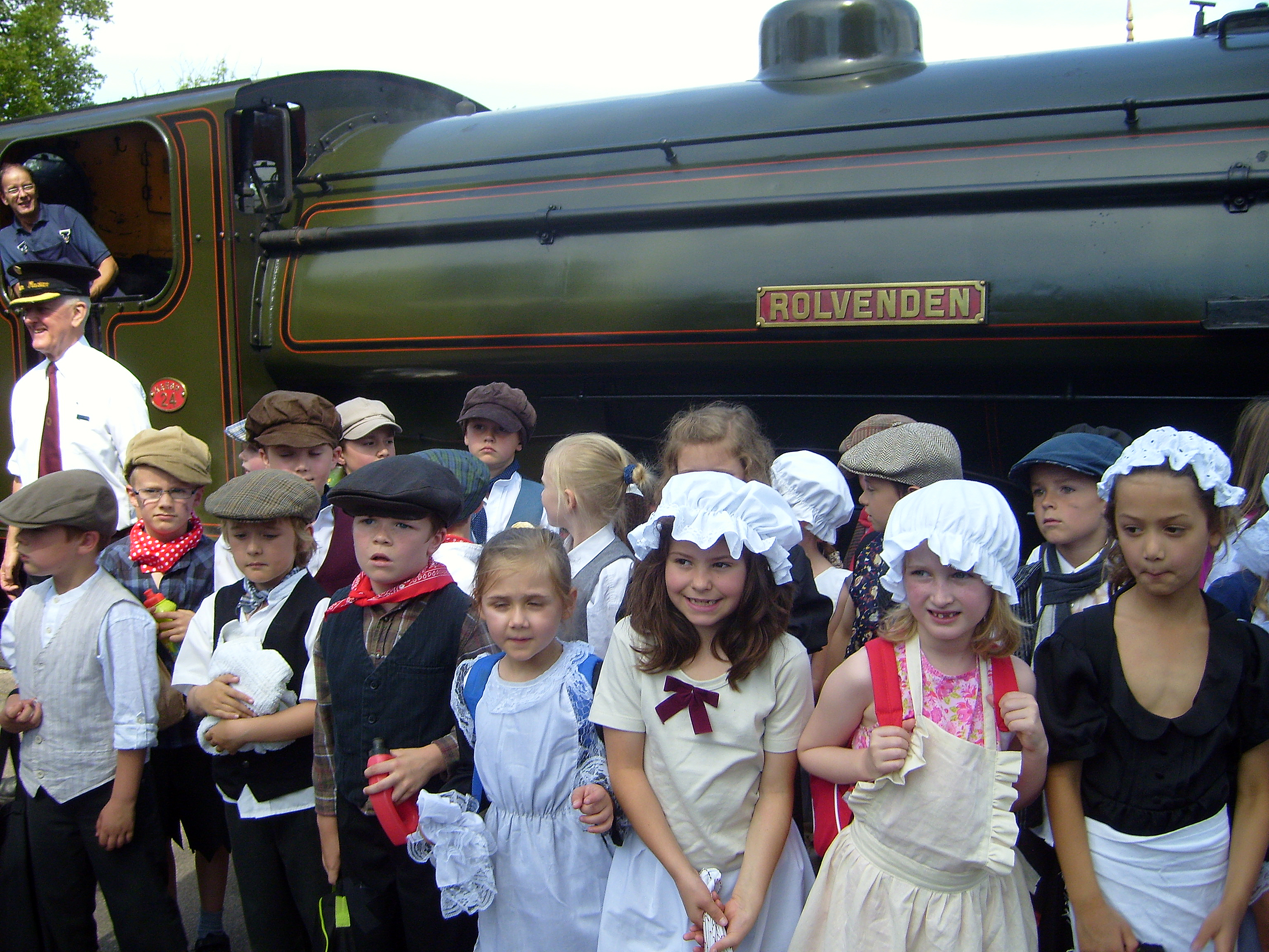 Boys and girls in Victorian costume pose by Rolvenden, a Victorian steam engine. It's scary by the engine!  (at the Kent and East Sussex Railway)