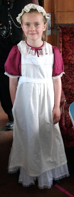 A 'Victorian' schoolgirl, looking very smart, poses in her long dress in a Victorian carriage (at the Kent and East Sussex Railway)