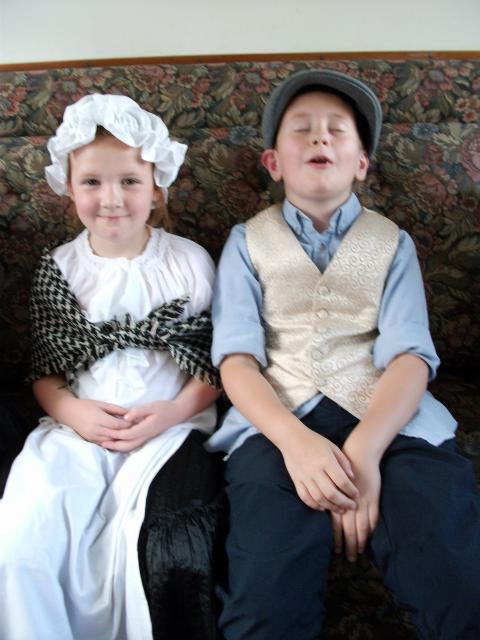 A boy and a girl children in costume pose in an authentic Victorian carriage during their Victorian experience day (at the Kent and East Sussex Railway)