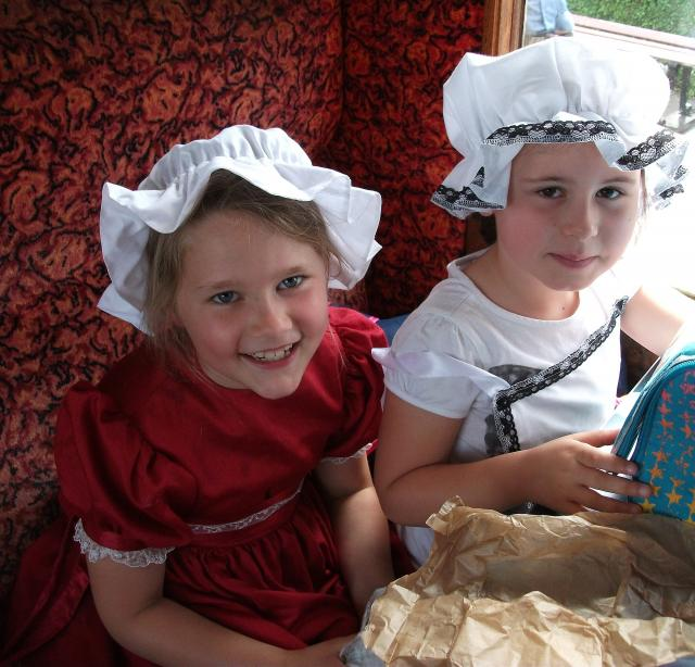 Two children in Victorian costume but in a modern carriage, compare it with their previous experience in a Victorian carriage (at the Kent and East Sussex Railway)