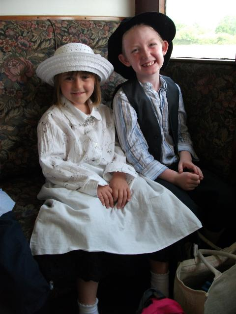 Two children in Victorian costume pose in a Victorian carriage  (at the Kent and East Sussex Railway)