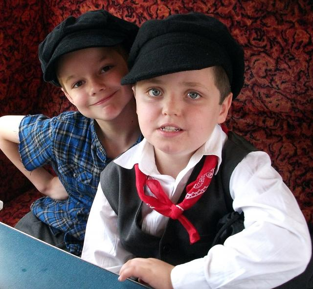 Two more boys in Victorian costume pose on a somewhat more modern carriage  (at the Kent and East Sussex Railway)