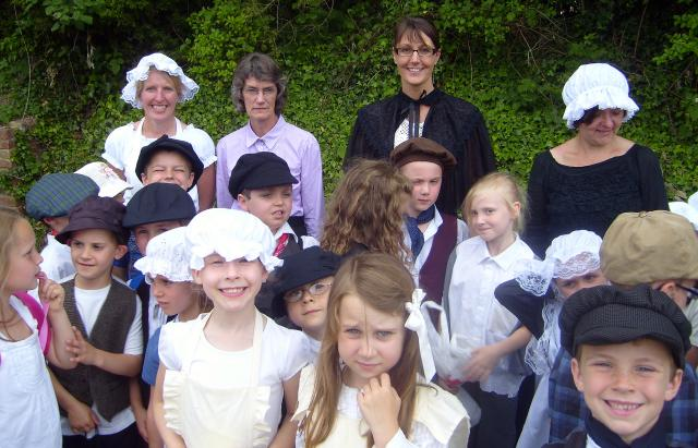 A Victorian school teacher poses with her children before the start of a Victorian Day  (at the Kent and East Sussex Railway)
