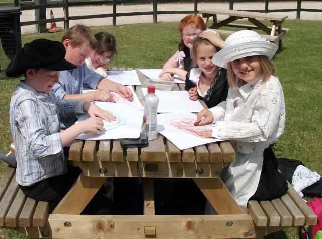 Children in Victorian costume, working hard on a sunny day as they  enjoy taking engine plate rubbings  (at the Kent and East Sussex Railway during a Victorian experience day)
