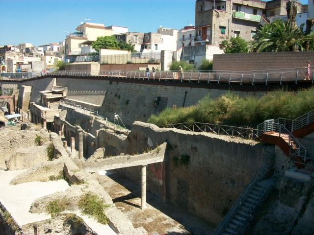 Herculaneum was an ancient Roman town destroyed by volcanic pyroclastic flows from Mount Vesuvius in 79 AD, along with other towns including Pompeii. The modern town of Ercolano now sits on top of much of the ancient buried city.