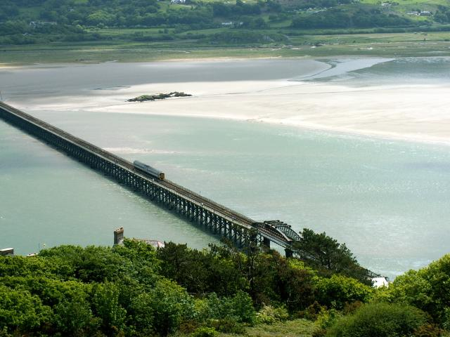 Barmouth Bridge is also known as the Barmouth Viaduct. It is a single-track wooden railway viaduct and carries the The Cambrian Coast Railway across the Mawddach estuary at Barmouth in Gwynedd, Wales.